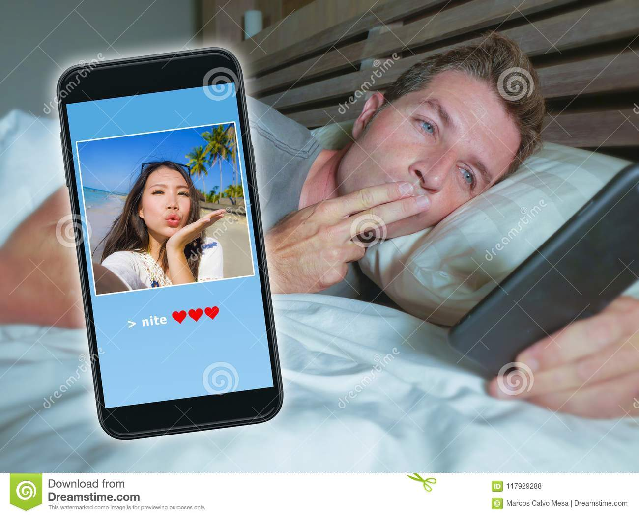 Man Lying On Bed Sending Good Night Kiss Text With Mobile Phone