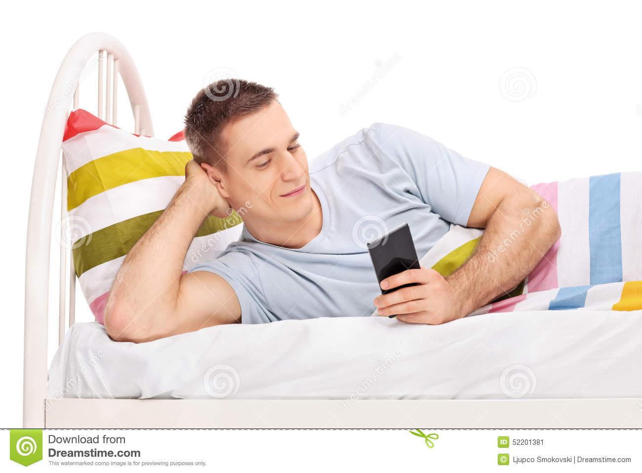 Man lying in bed and surfing on his cell phone stock photo for Cell phone bed