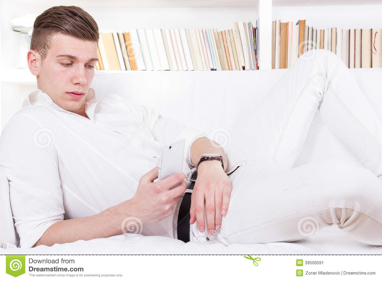 Man lying on the couch texting message on cellphone
