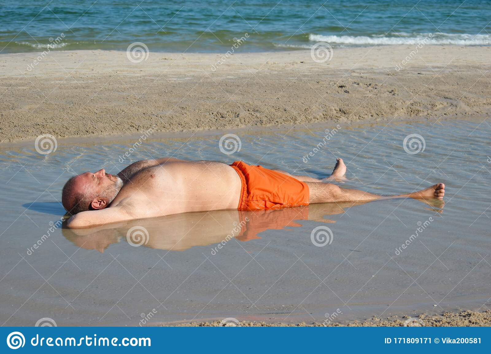 The Man In The Puddle On The Beach Relaxing Holiday By The Sea Fun Beach Photo The Fat Man In The Sea Stock Image Image Of Large Lying 171809171