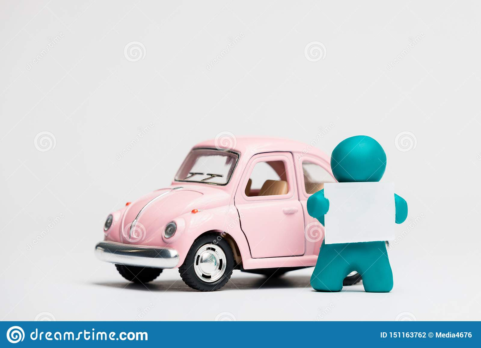 A man made from plasticine holding a blank sheet of paper next to a car on white background