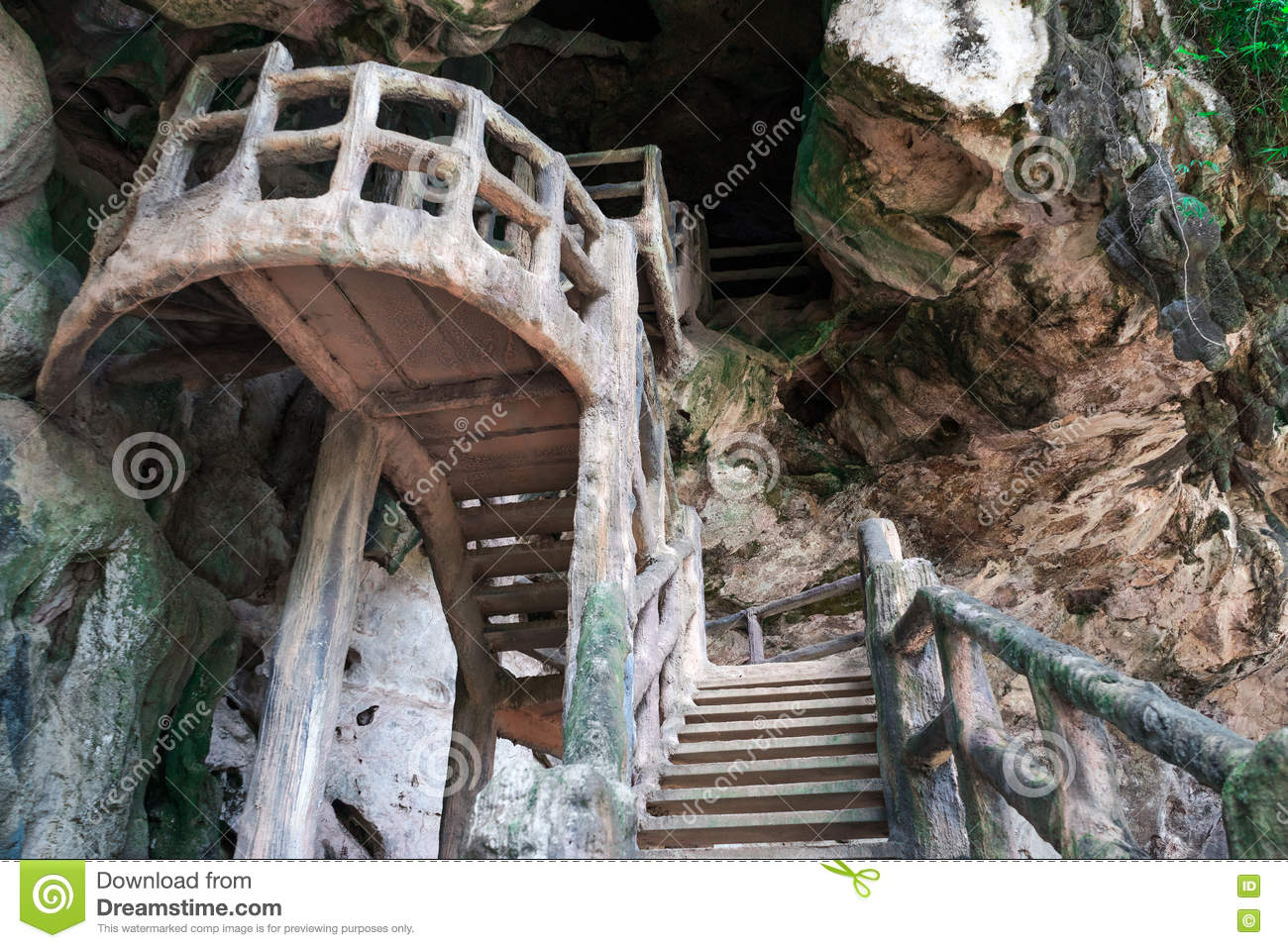 Man made stairs upto dark cave on rocky cliff