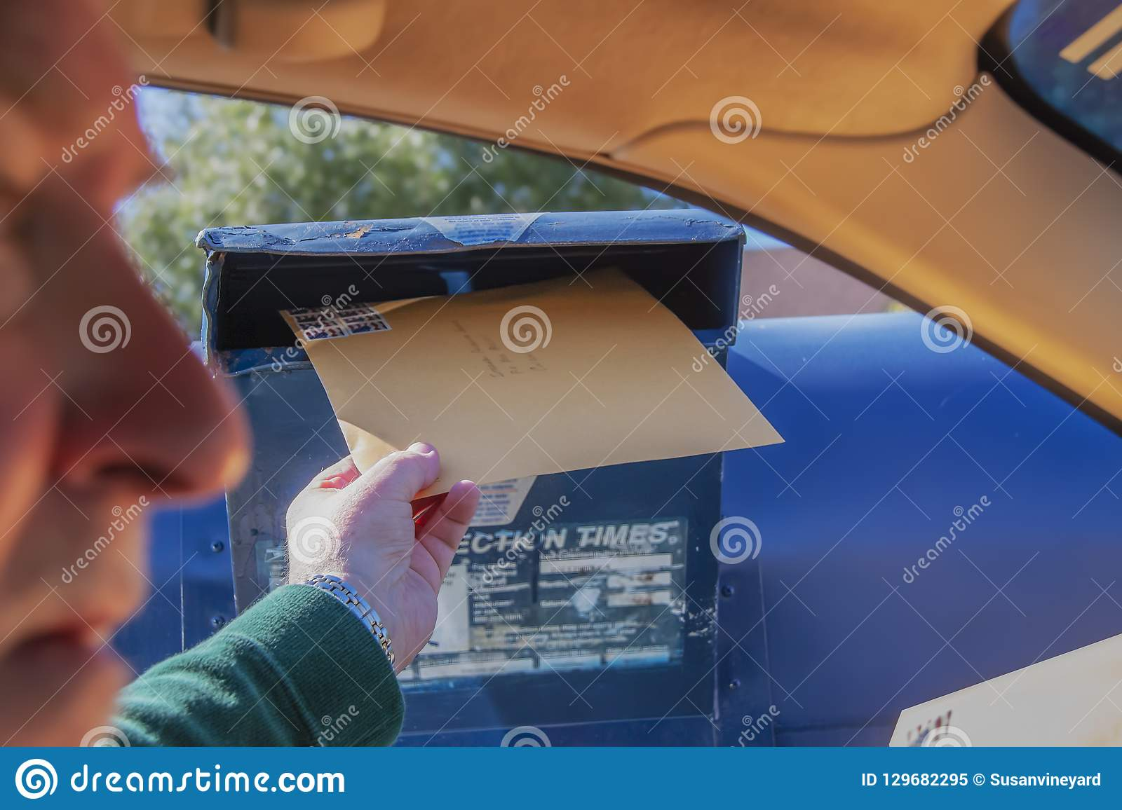 Man mailing tax return - large envelope at drive by mailbox with face blurred - selective focus