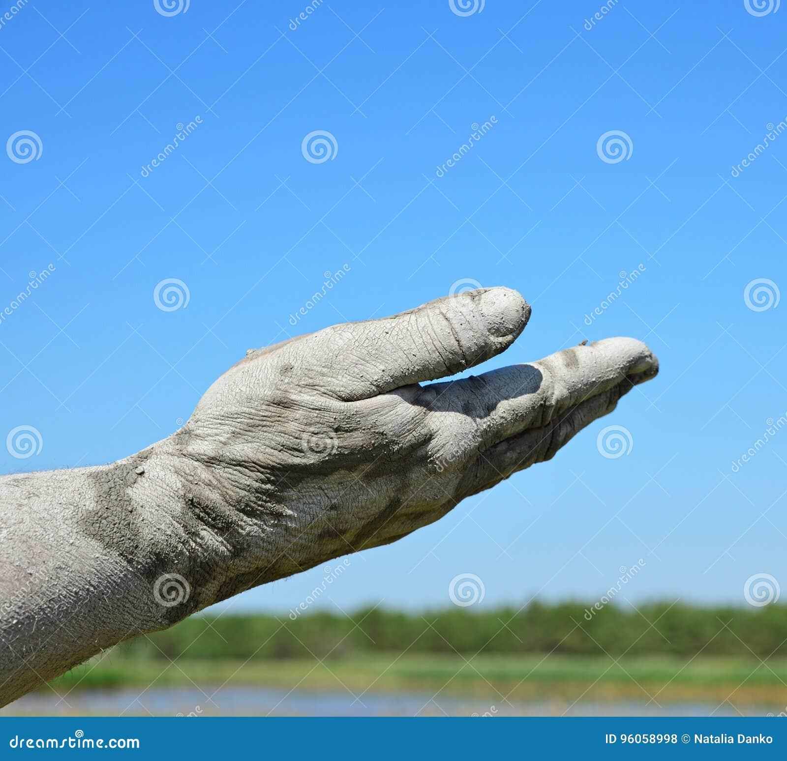 Man& x27 ; main de s dans l en avant prolongé de boue