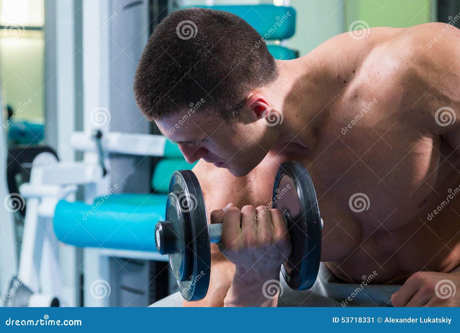 Man makes exercises dumbbells