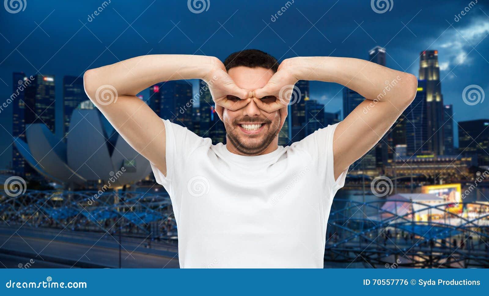 Man making finger glasses over city background