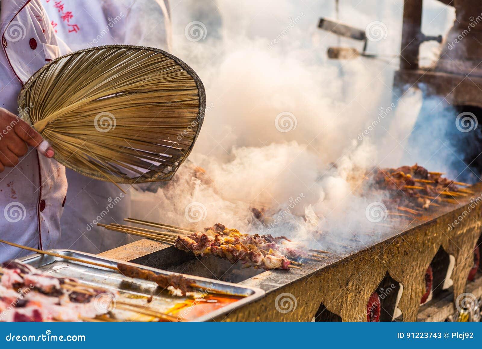Man matlagningsteknålar på en traditionell marknad i Chengdu - Kina