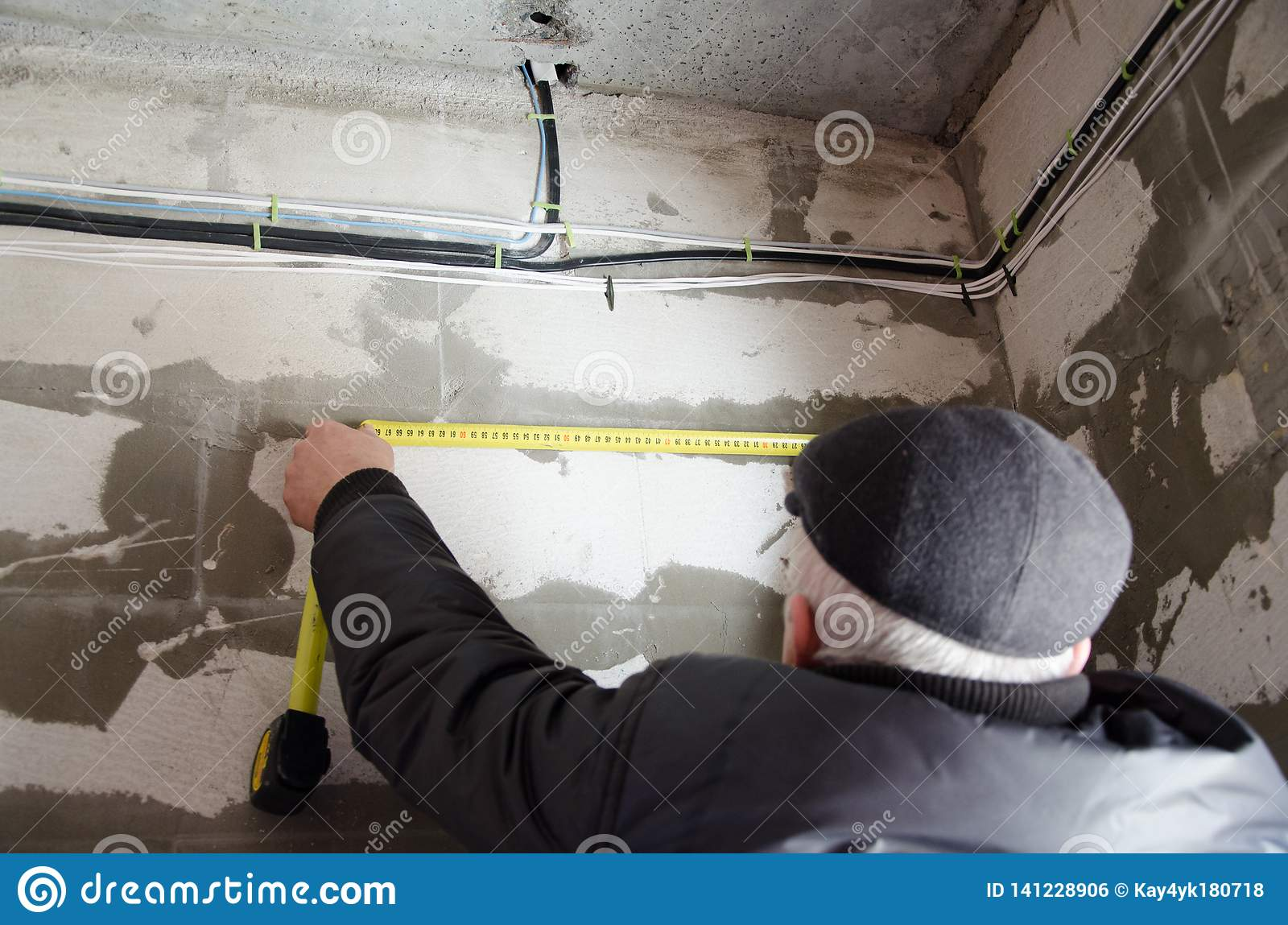 A man measures the wiring, accuracy is important