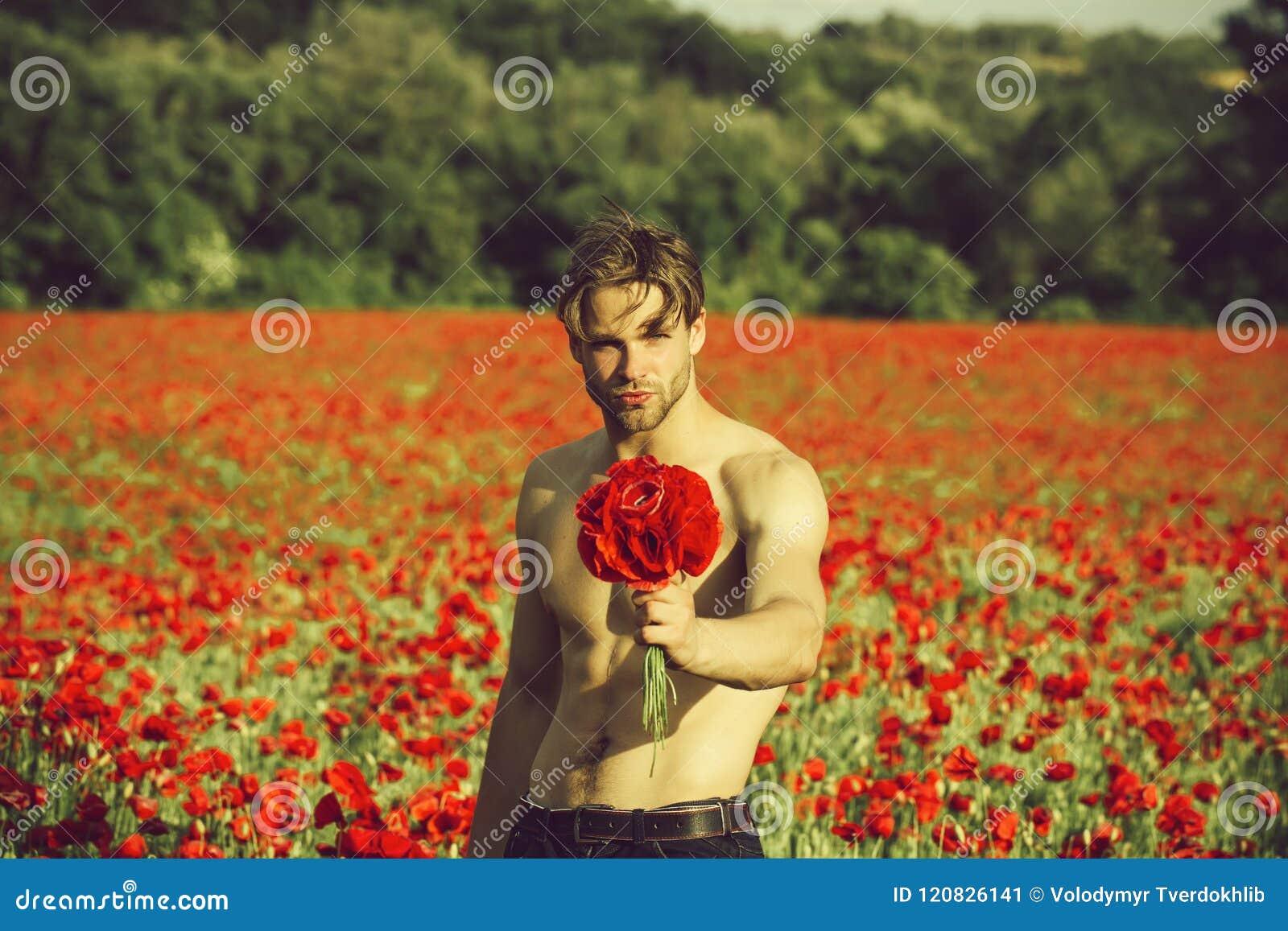 Man med blommor grabb med den muskulösa kroppen i fält av röd vallmofrö