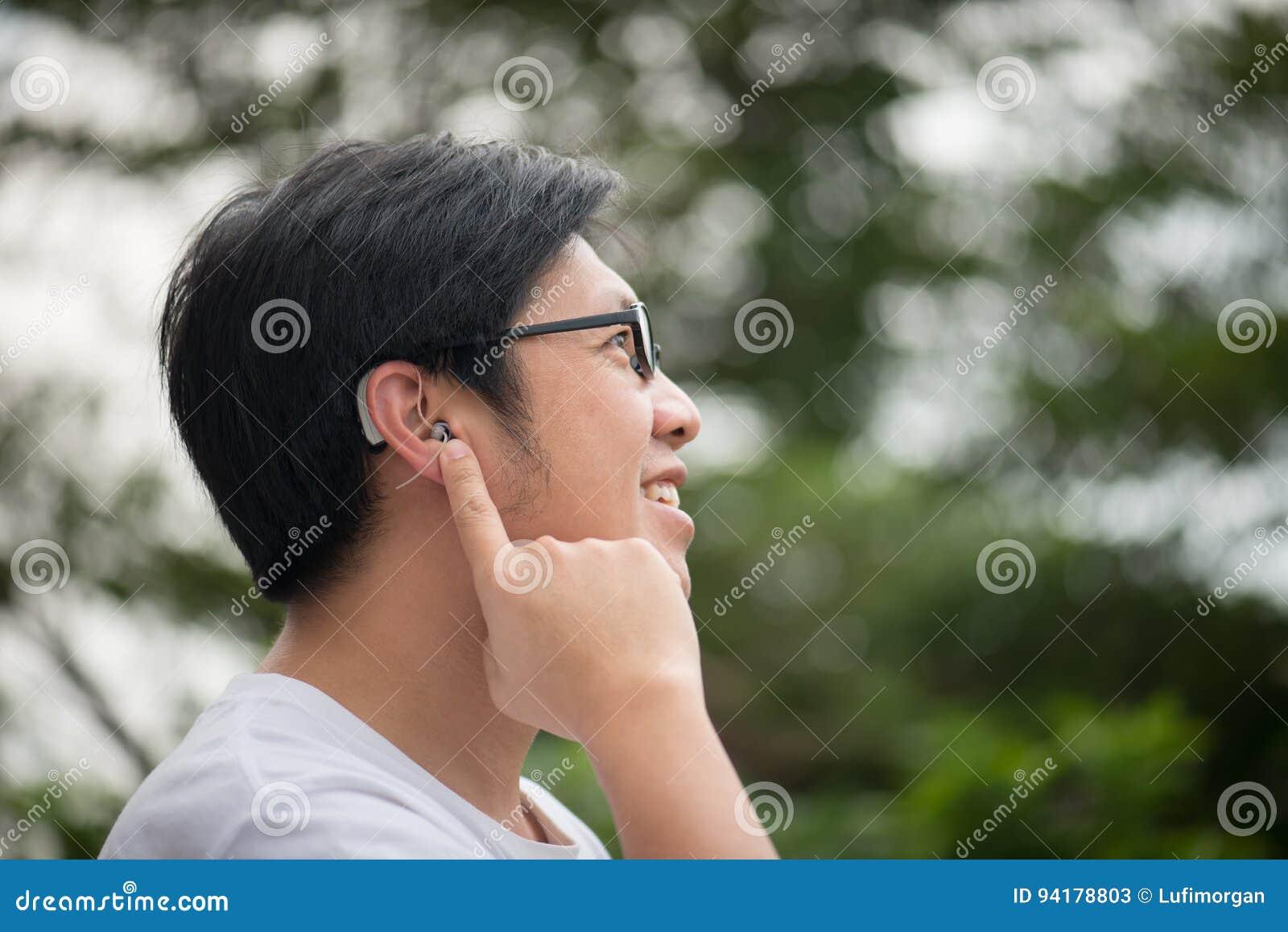 Man med hörapparat bak örat