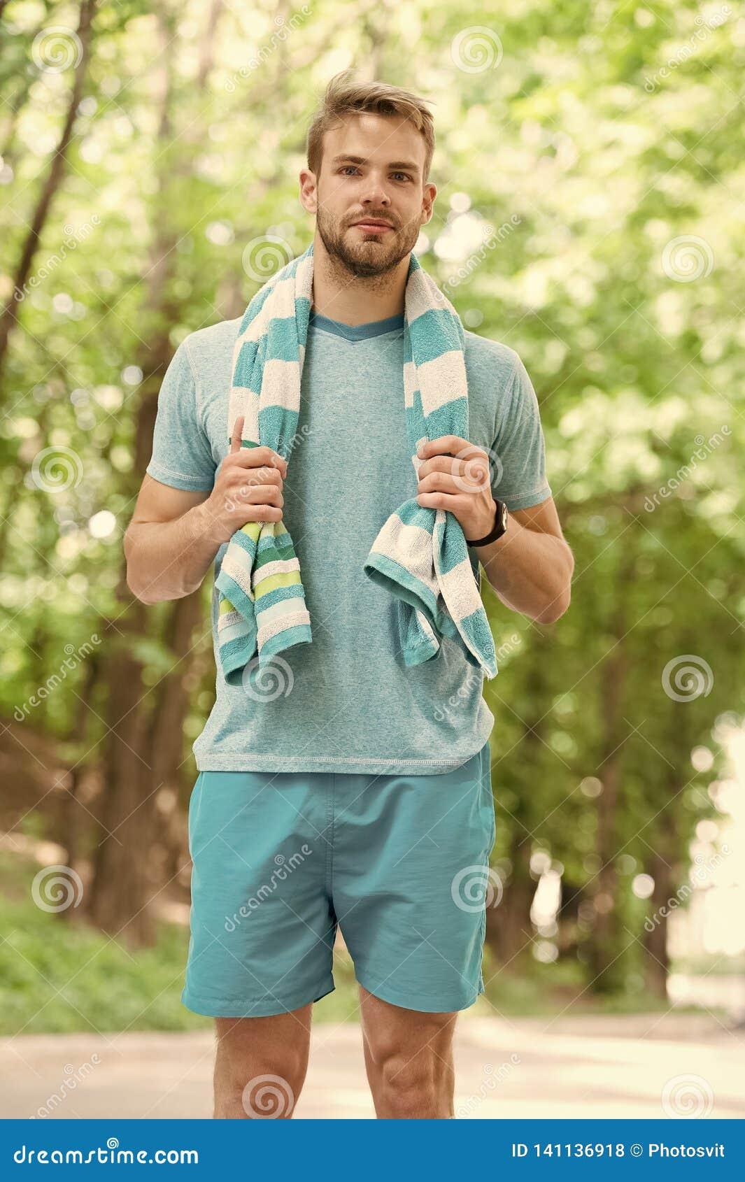Man med handduken på naturligt landskap Idrottsman, precis når utbildning svettigt trött Sommarstrandtid och semester