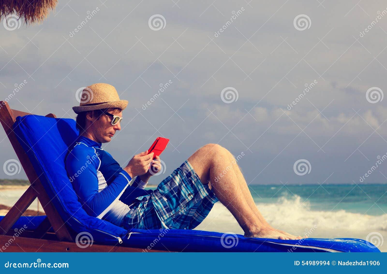 Man med handlagblocket på strandsemester