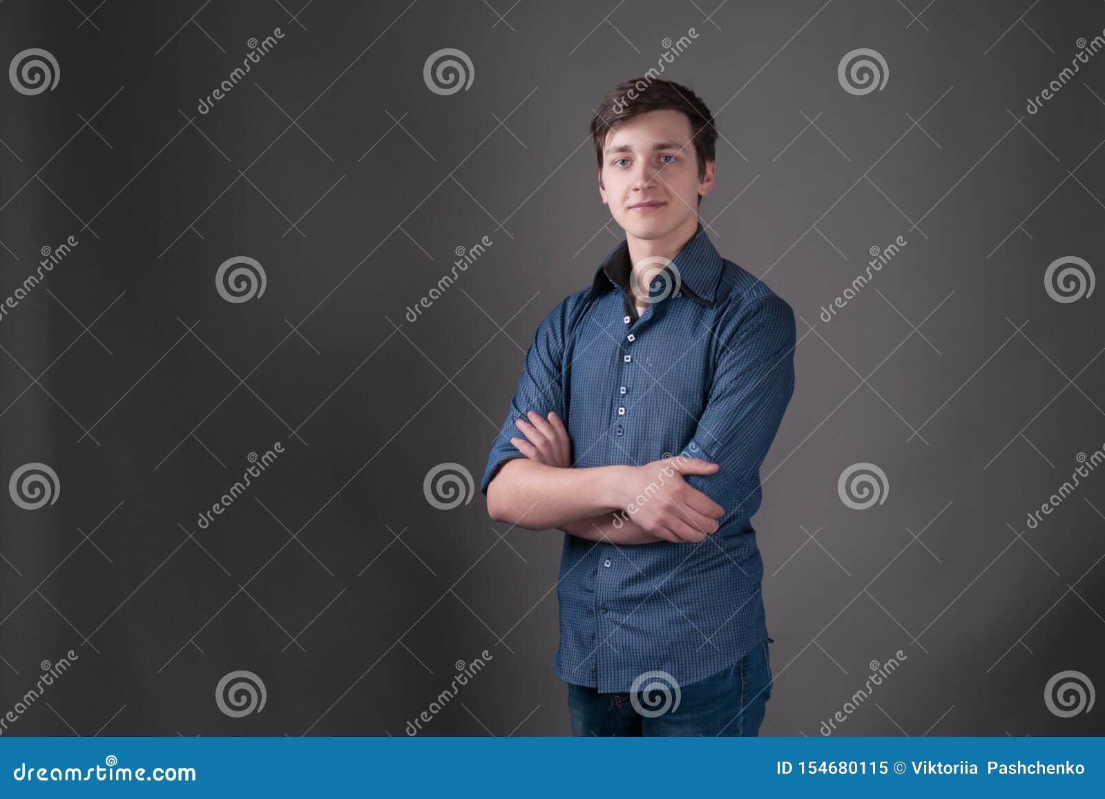 Man med mörkt hår i blått skjortaanseende med korsade armar