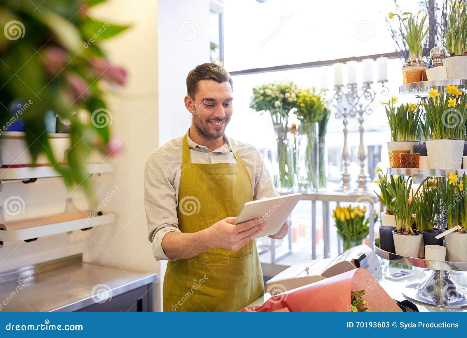 Man med minnestavlaPCdatoren på blomsterhandeln