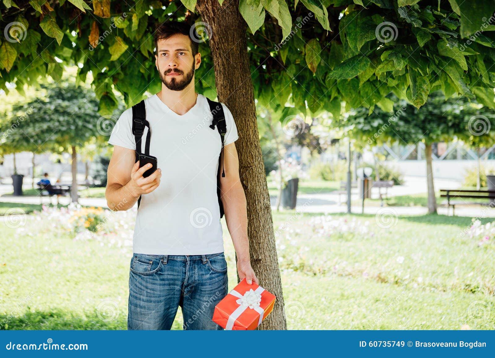 Man med ryggsäcken och en gåva bredvid ett träd