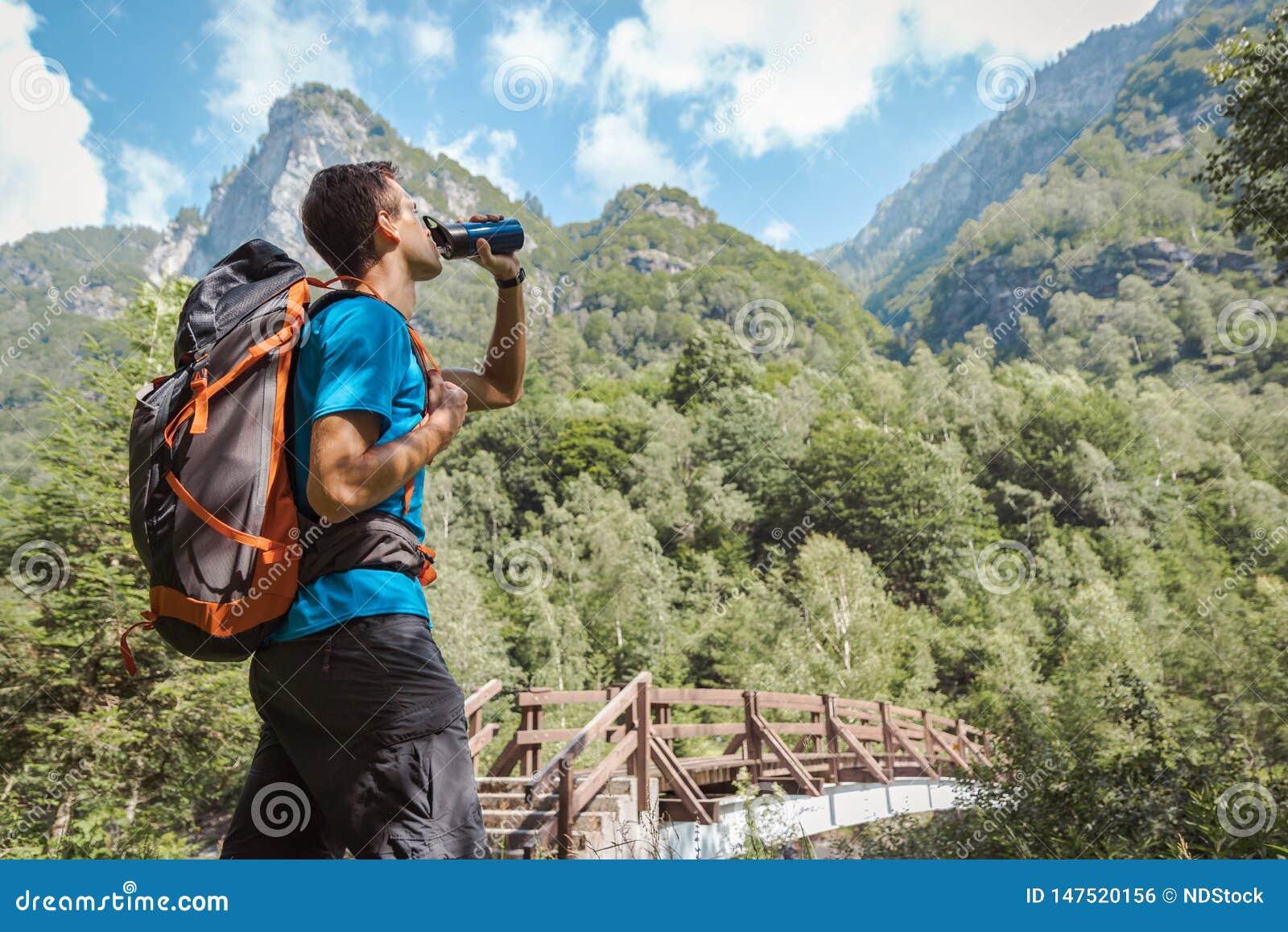Man med ryggsäcken som dricker från vattenflaskan som omges, genom att göra häpen naturen