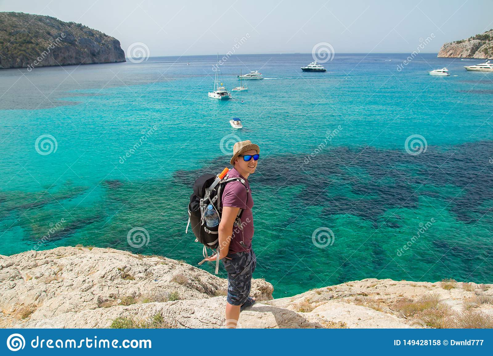 Man med ryggs?cken som g?r p? klippor ovanf?r havet