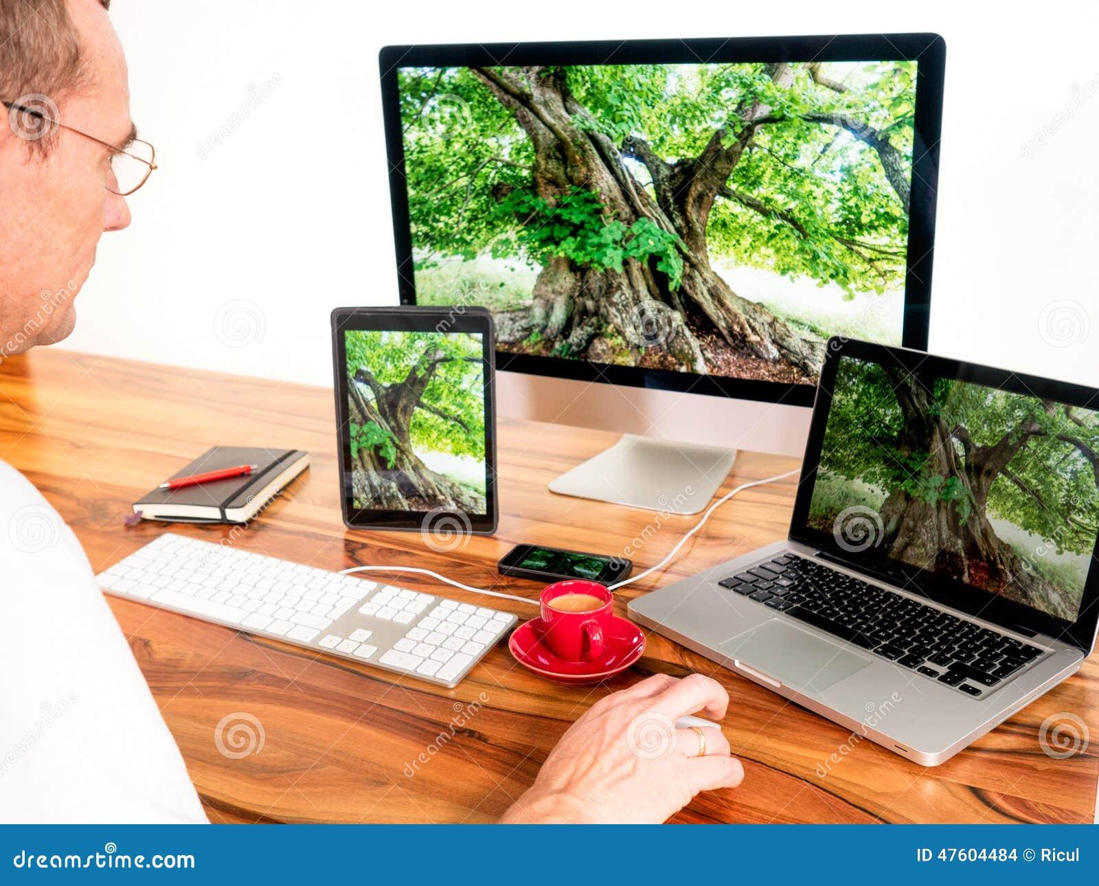 Man med sammankopplade datorer och mobila enheter