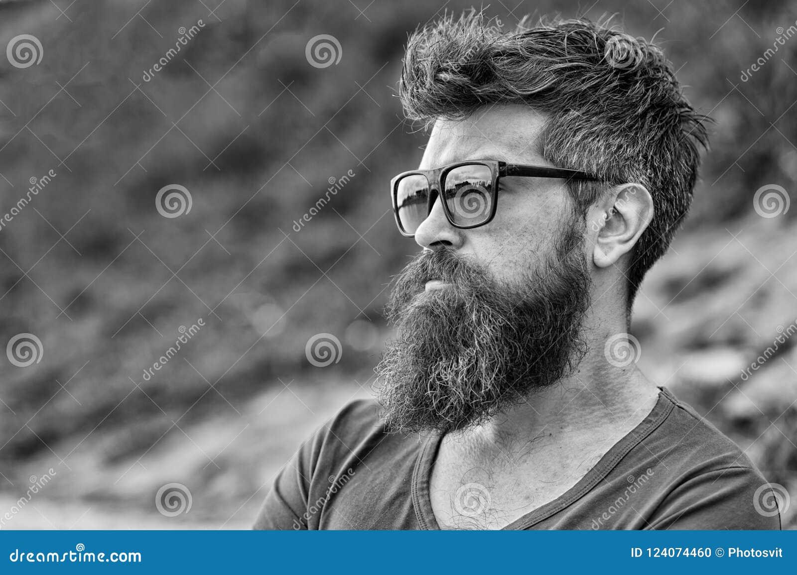 Man med skägget och mustasch på den strikta framsidan, naturbakgrund som är defocused Den skäggiga mannen bär modern solglasögon
