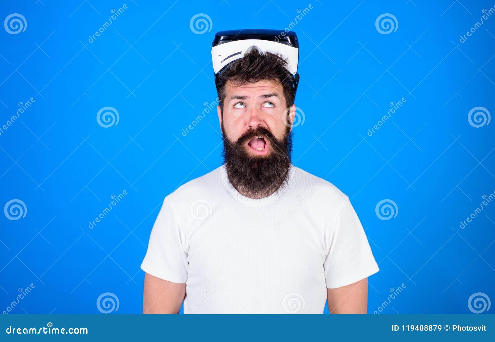 Man med skägget och mustaschen med VR-exponeringsglas, blå bakgrund Grabb med VR-exponeringsglas eller head monterad skärm Hipste