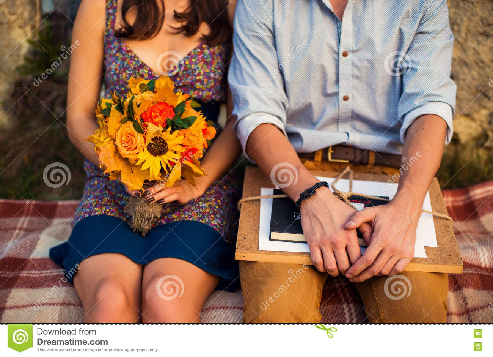 Man med sketchbooken och kvinna med ett bukettsammanträde på en pläd
