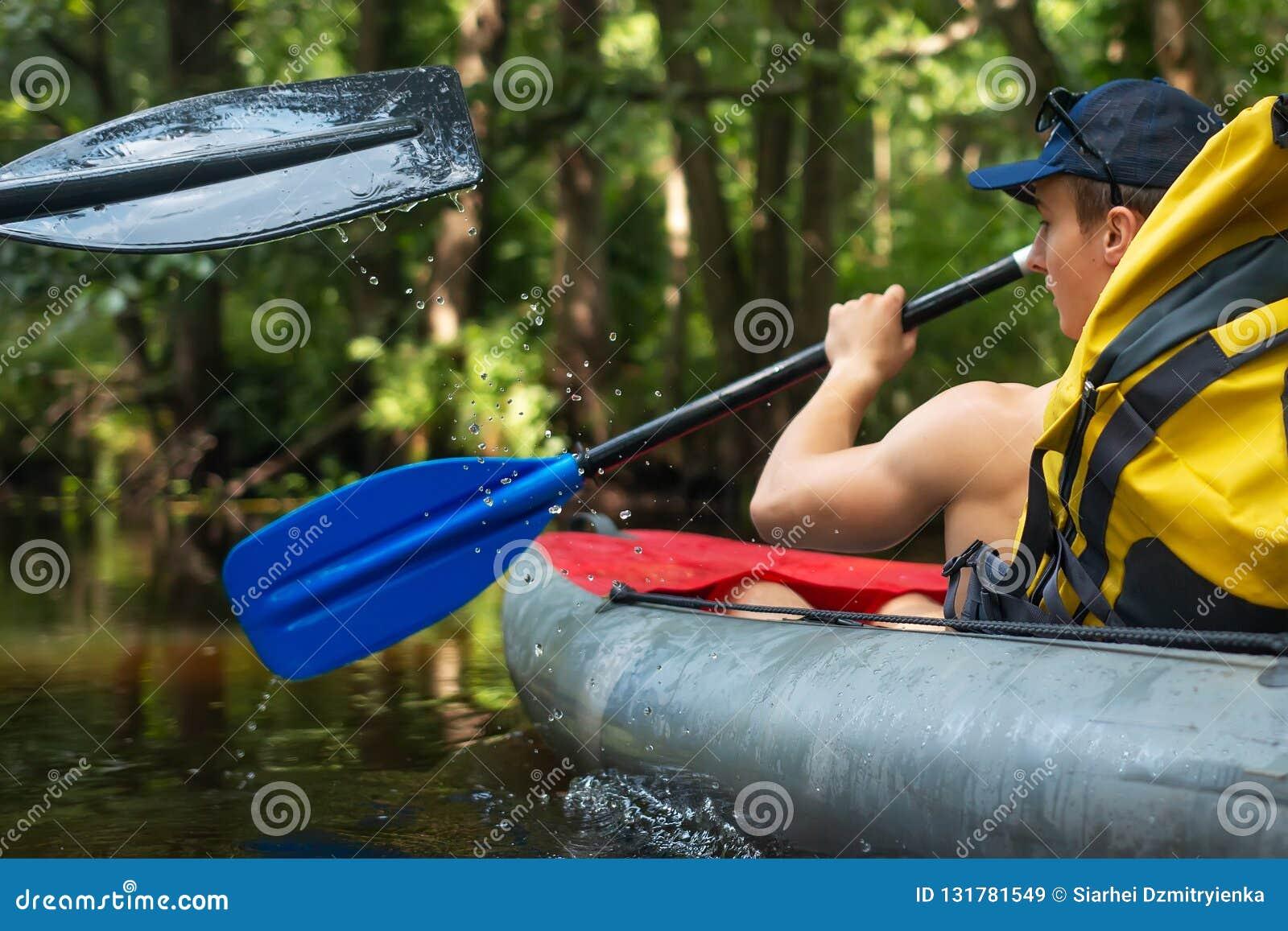Man med skovlar i kajakbad längs jaunglefloden