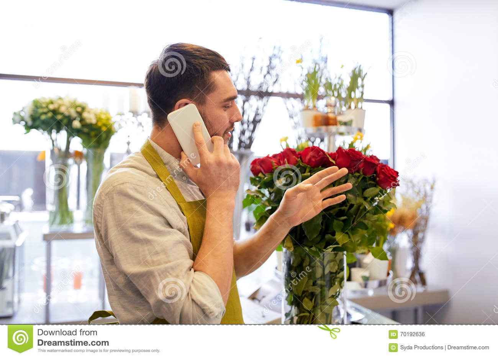 Man med smartphonen och röda rosor på blomsterhandeln