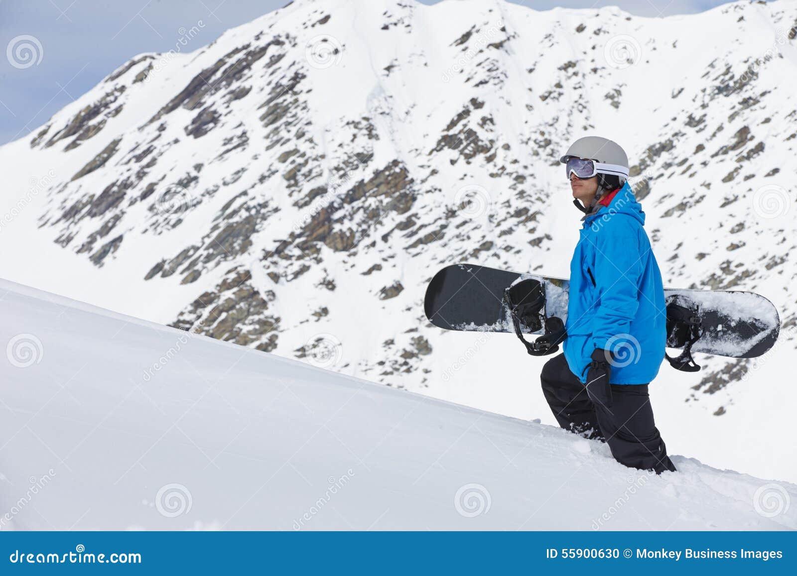 Man med snowboarden på Ski Holiday In Mountains