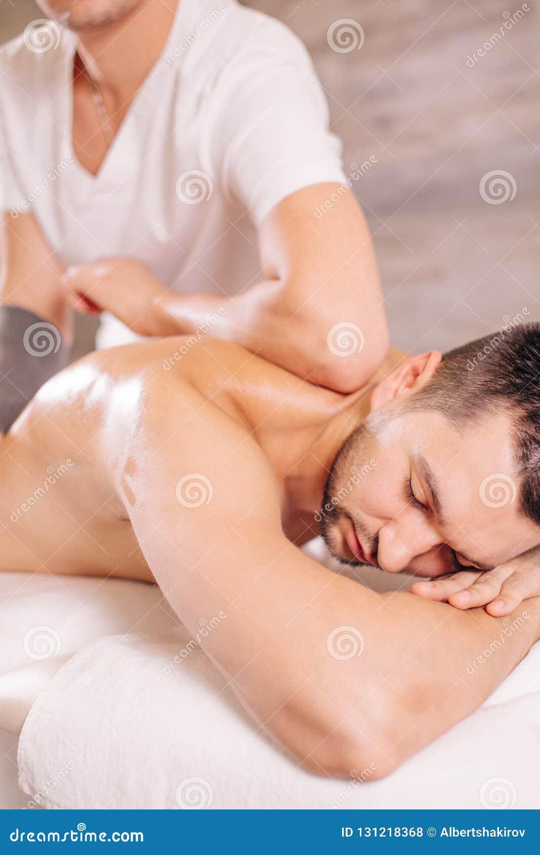 Man med stängda ögon som ligger på sängen och får massagen för öm baksida
