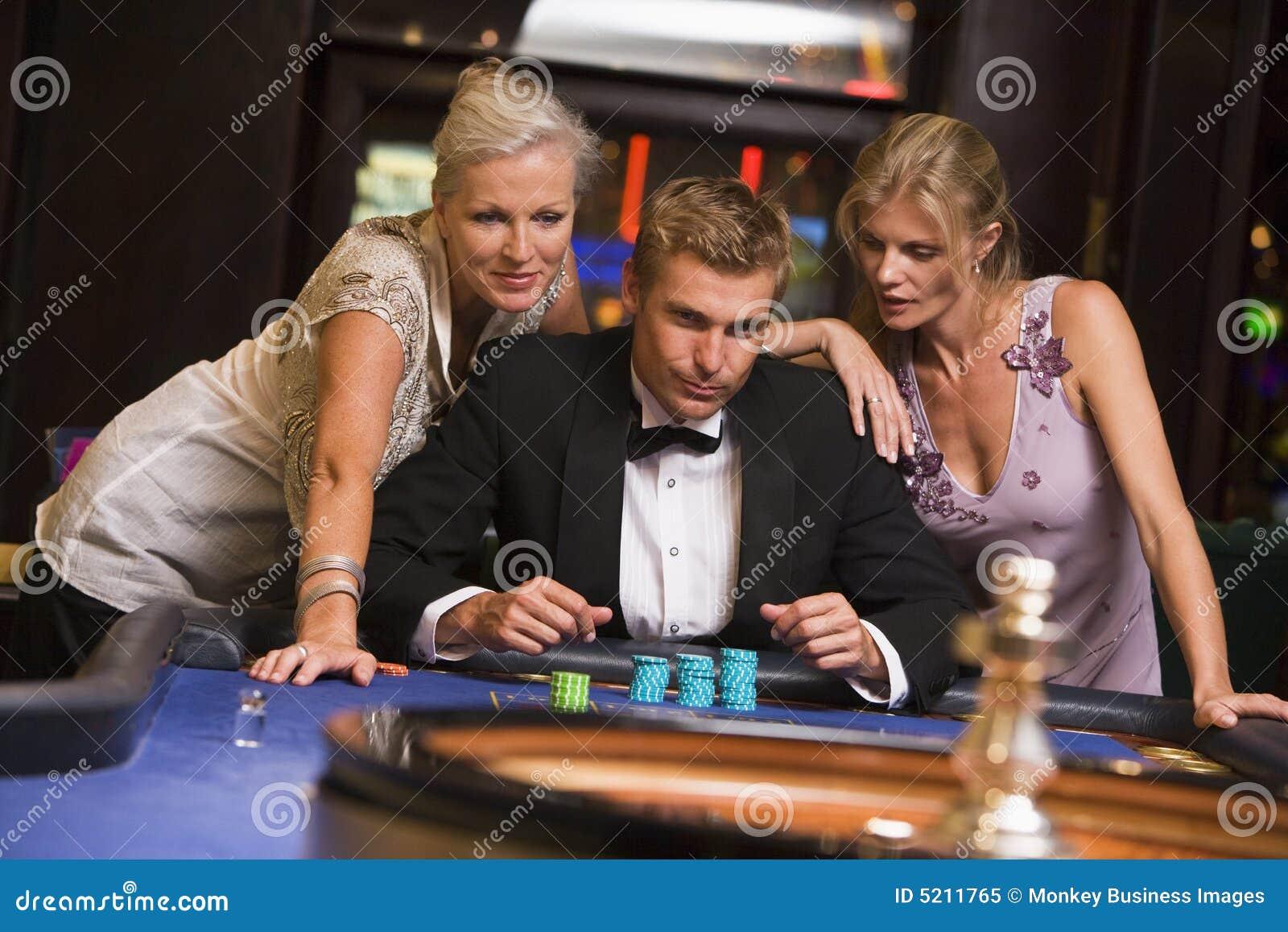 Man Met Betoverende Vrouwen In Casino Stock Afbeelding