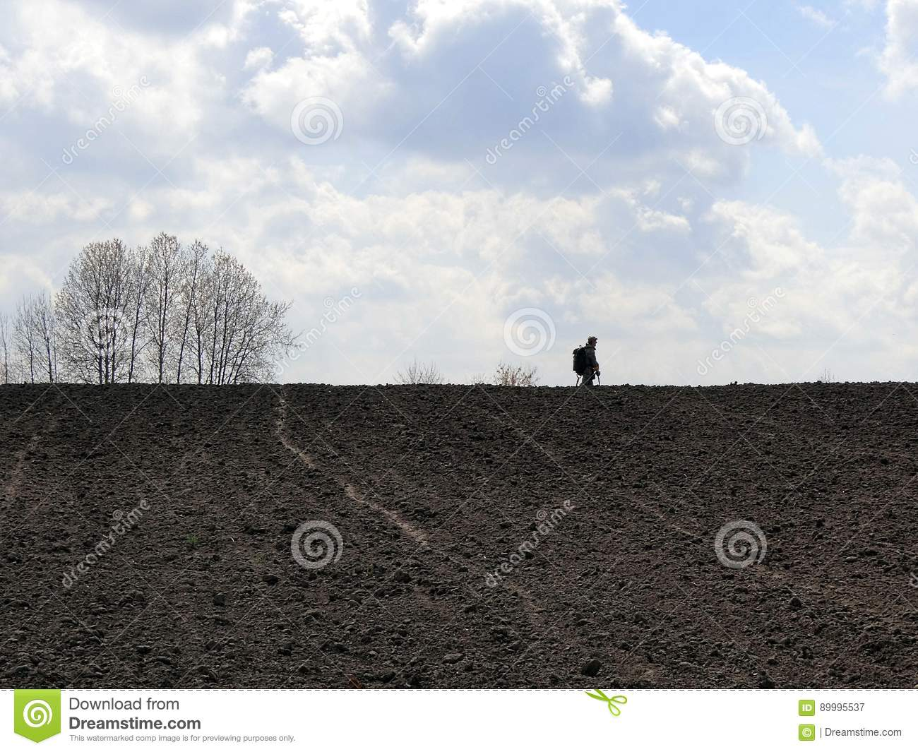 Jew Detector: A Man With A Metal Detector On A Plowed Field, Against A