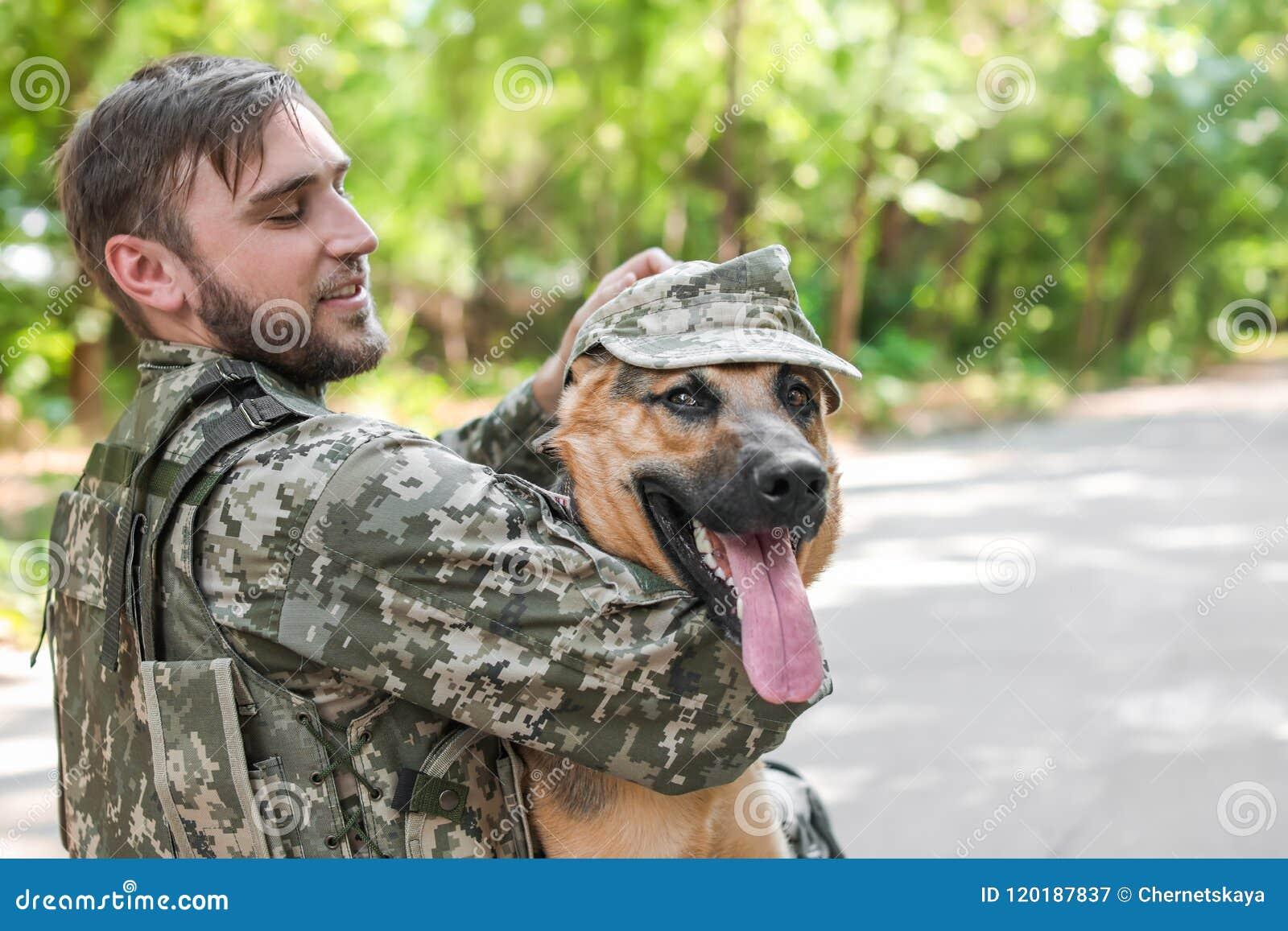 Man in military uniform with German shepherd dog