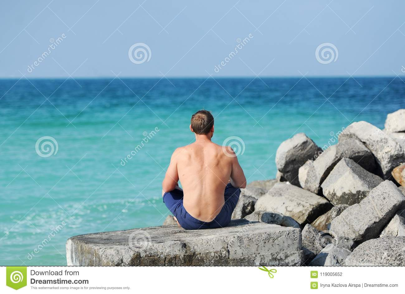 The man with a naked torso sitting on a stone with her back looking at the sea