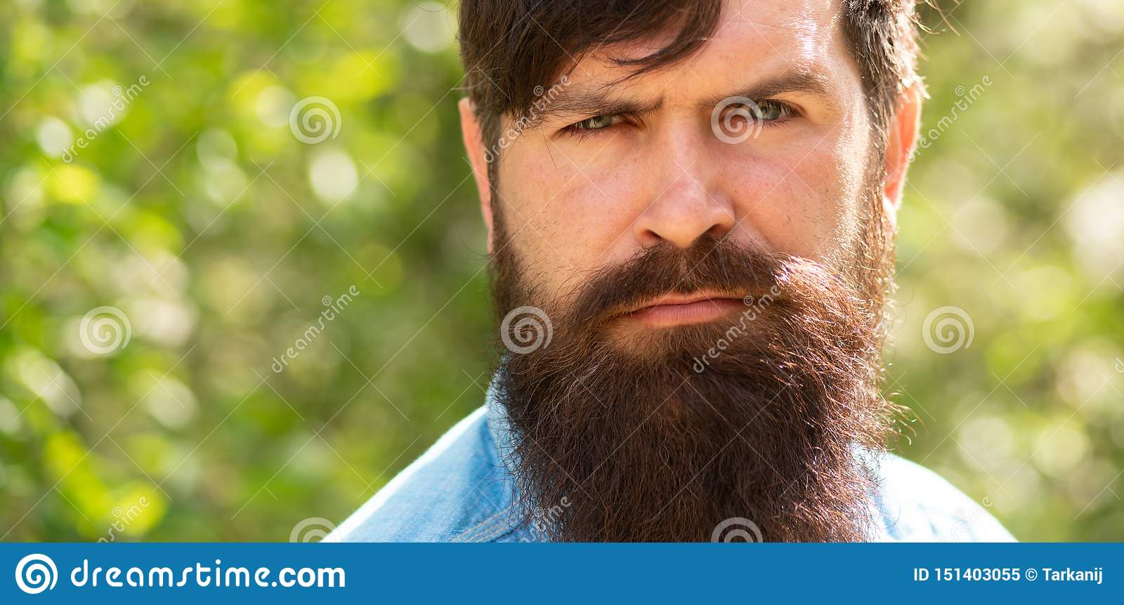 Man on nature background. Bearded guy. Young male hipster. Attractive man with green eyes. Male portrait. Handsome guy