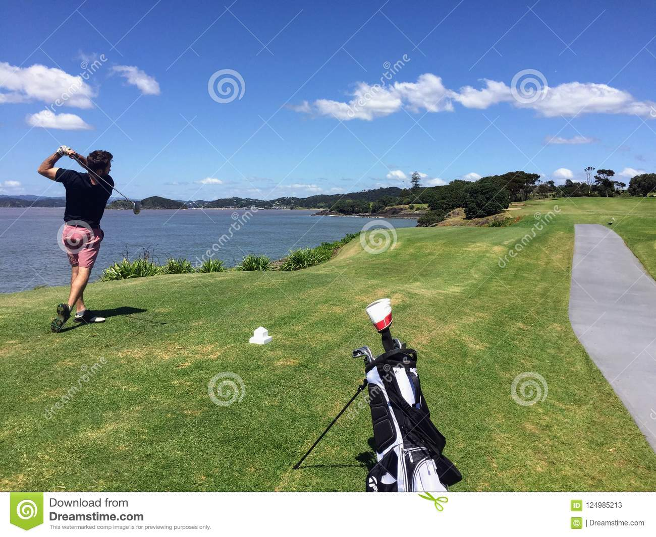 Man with a nice follow through playing golf along the coast of n