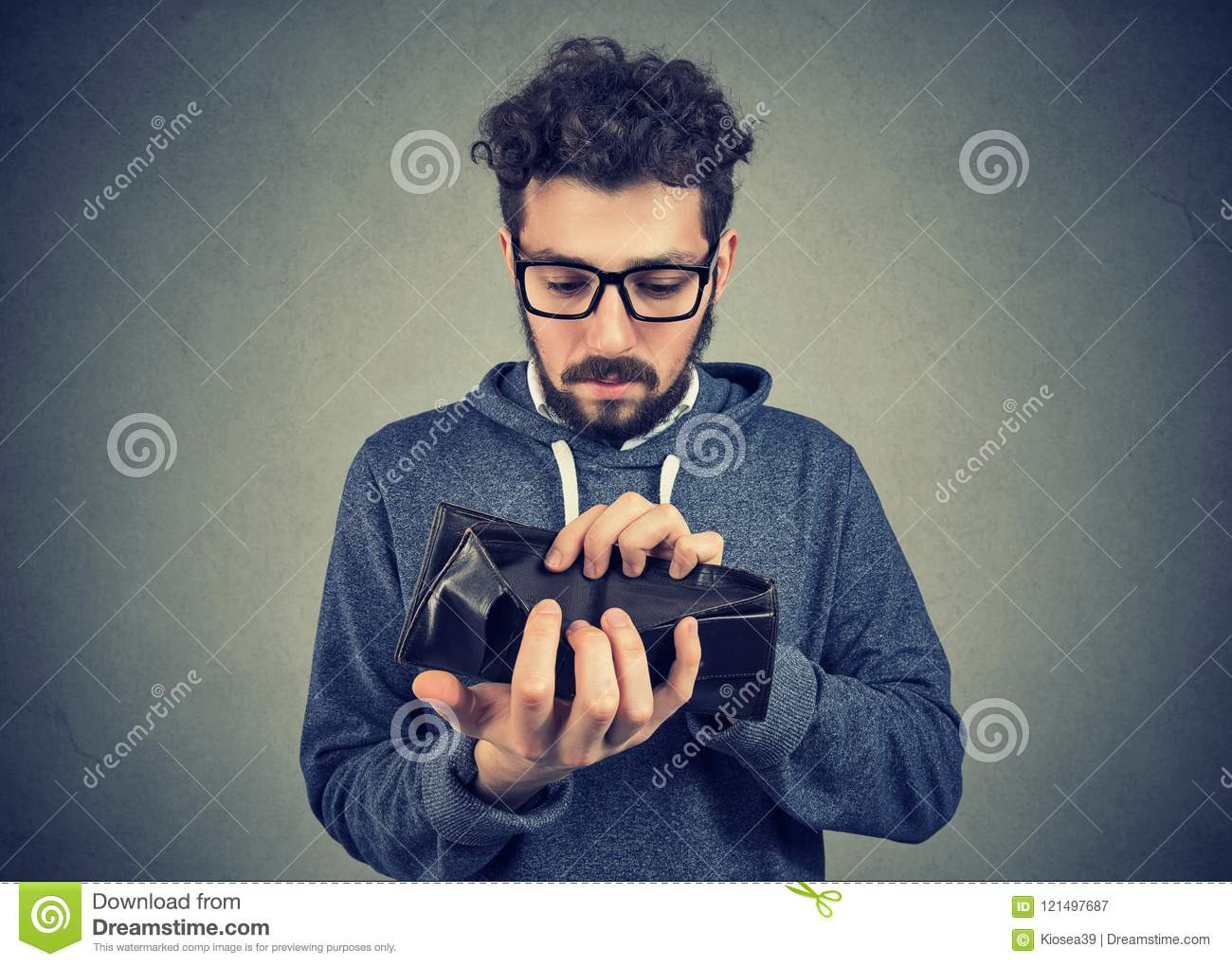Man with no money holding an empty wallet