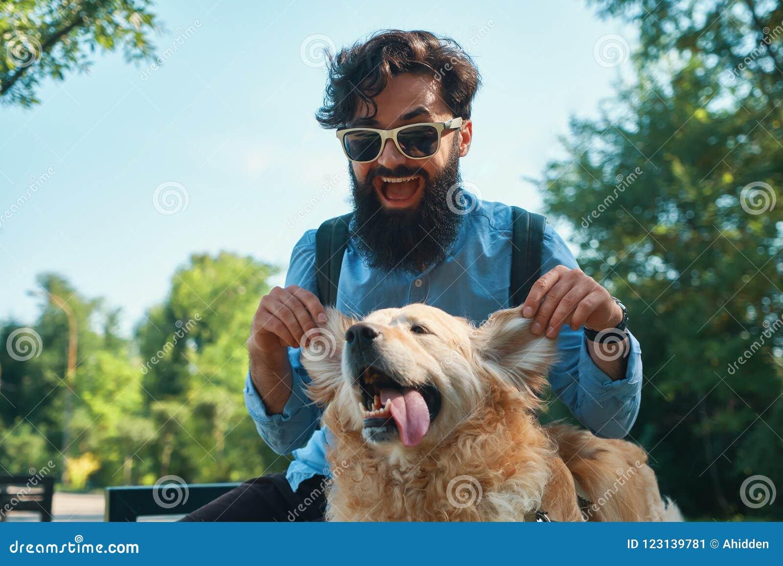 Man och hund som har gyckel, spela som gör roliga framsidor medan restin