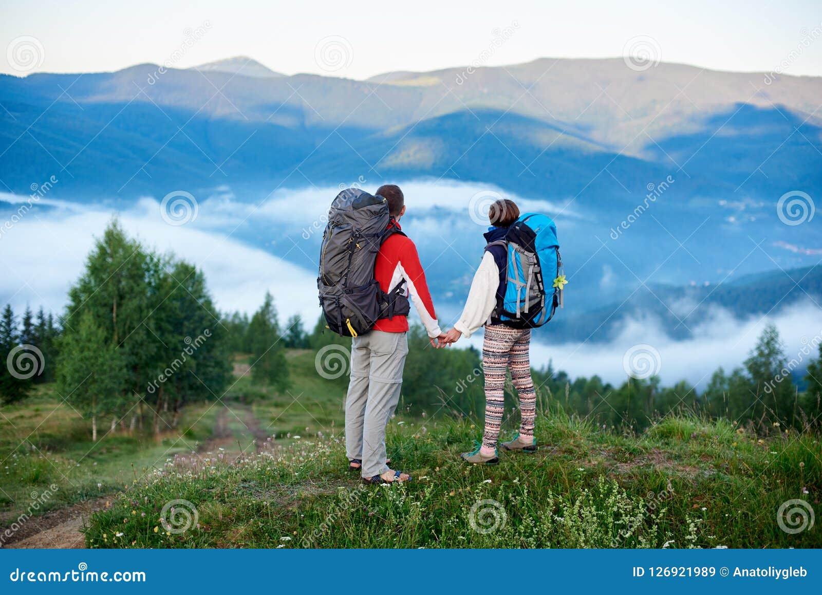 Man och kvinna för bakre sikt med ryggsäckar som överst rymmer händer av kullen med sikt av berg
