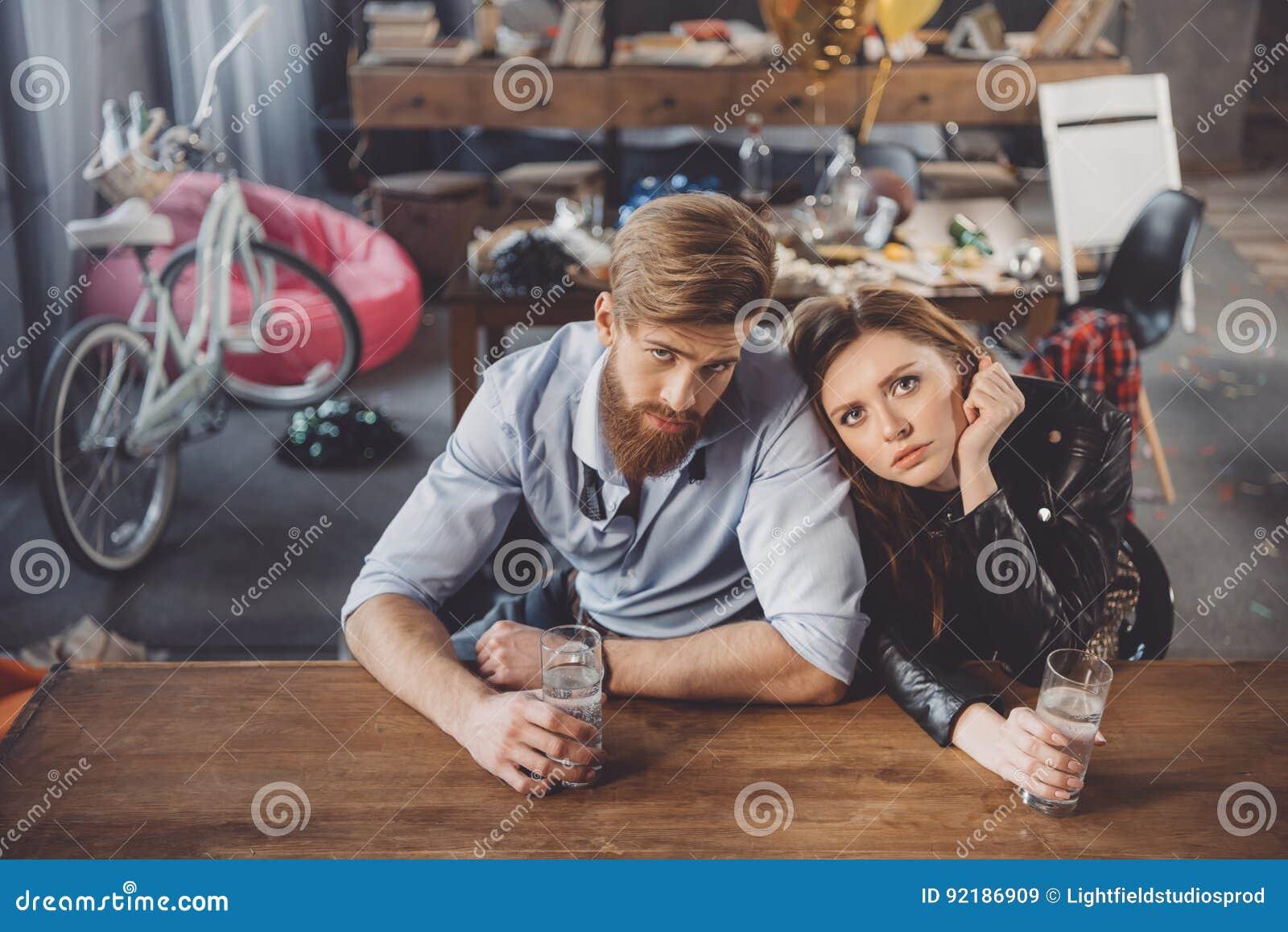 Man och kvinna med bakrus med mediciner i smutsigt rum