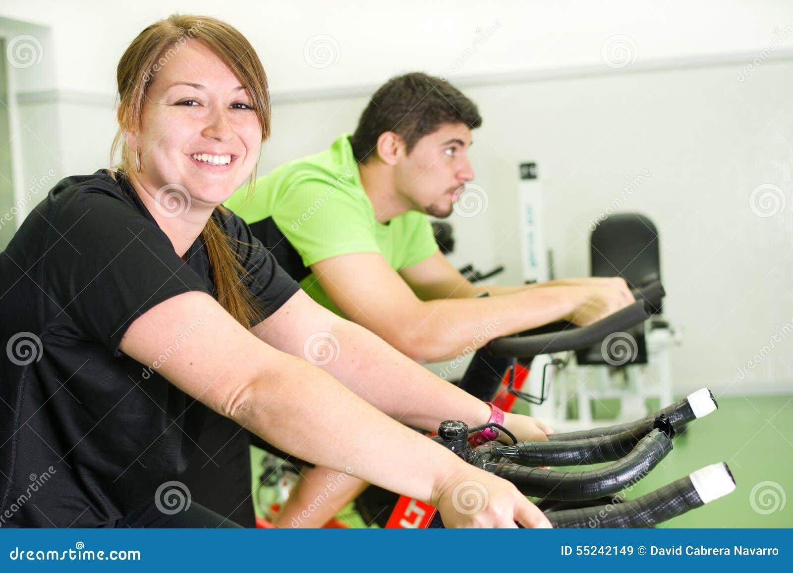 Man och kvinna med den stationära cykeln i idrottshall