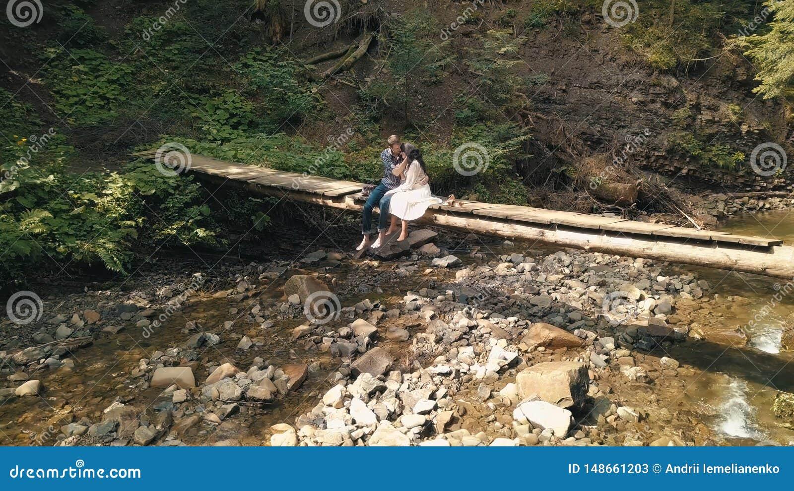 Man och kvinna som ?r f?r?lskade p? en bro ?ver floden i skog