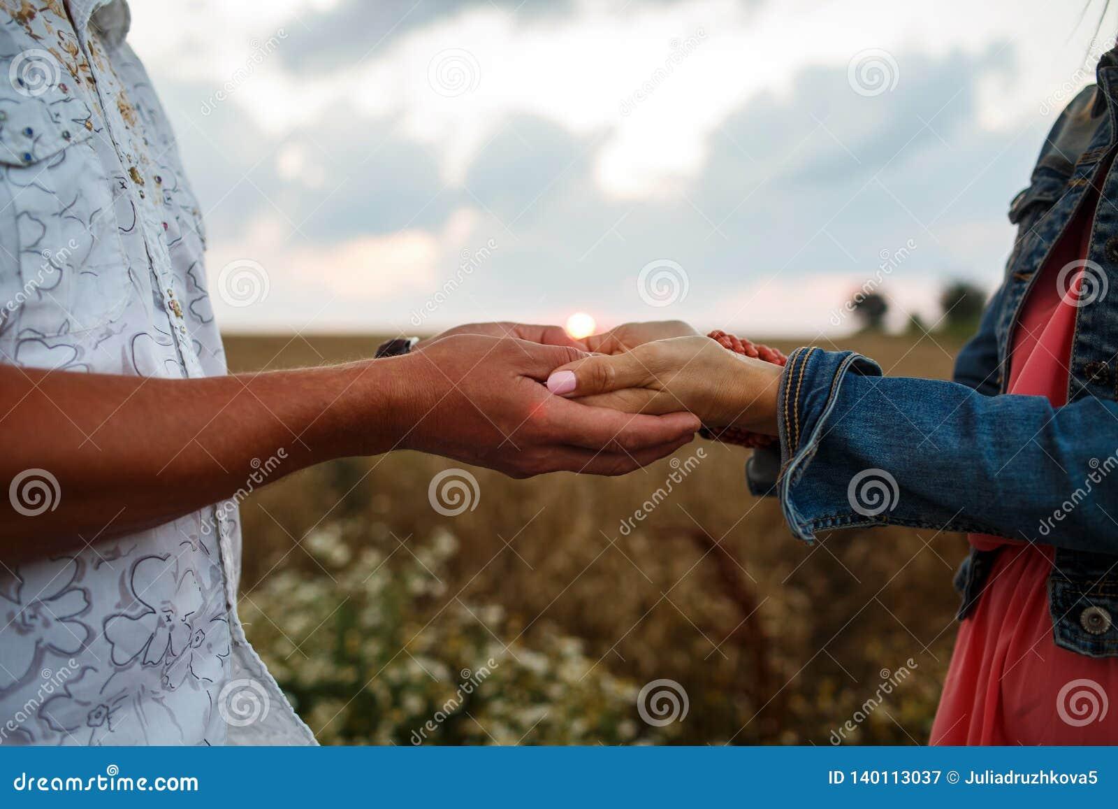 Man och kvinna som rymmer händer som går i fältet på solnedgången