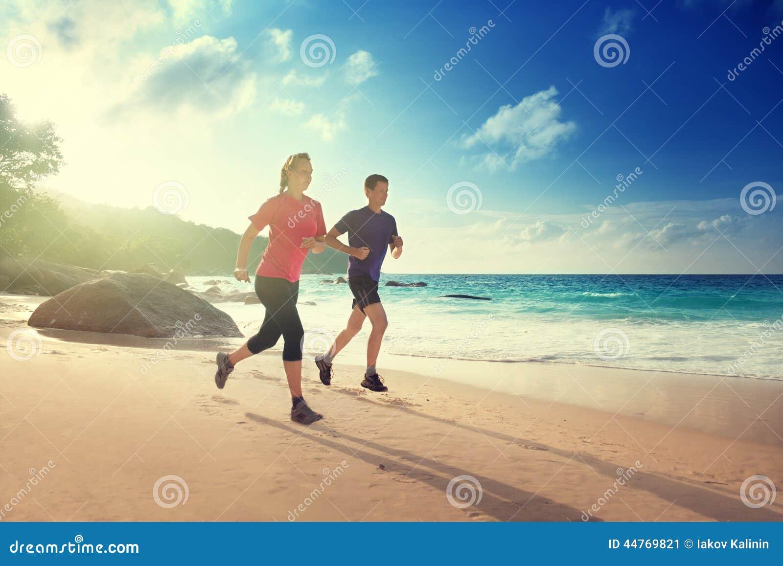 Man- och kvinnaspring på den tropiska stranden