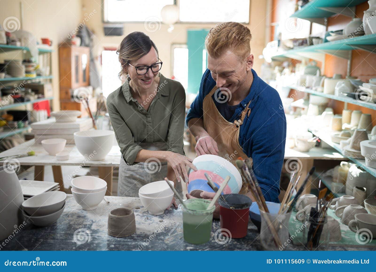 Man och kvinnlig keramiker som påverkar varandra med de