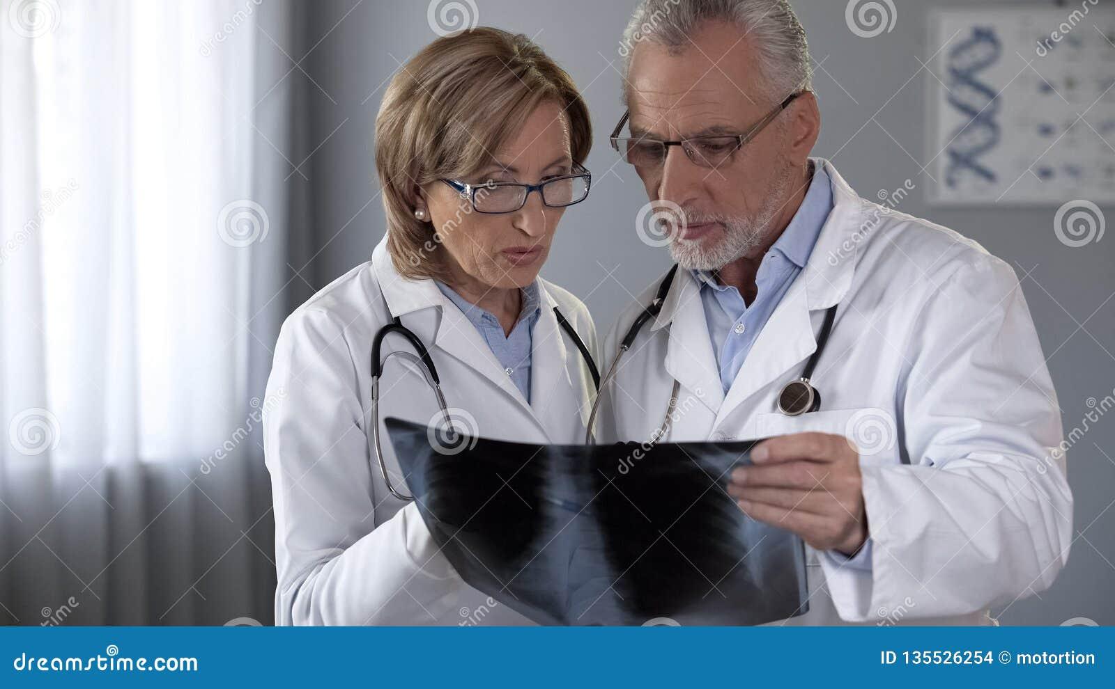 Man och kvinnliga doktorer som ser lungaröntgenstrålen som diskuterar lunginflammationdiagnos