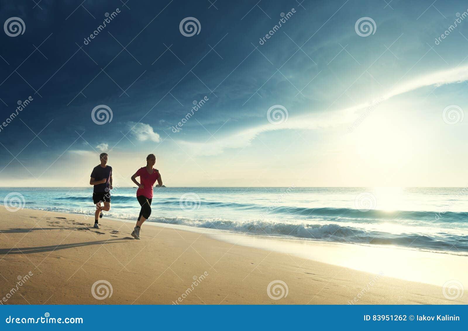 Man och kvinnor som kör på den tropiska stranden