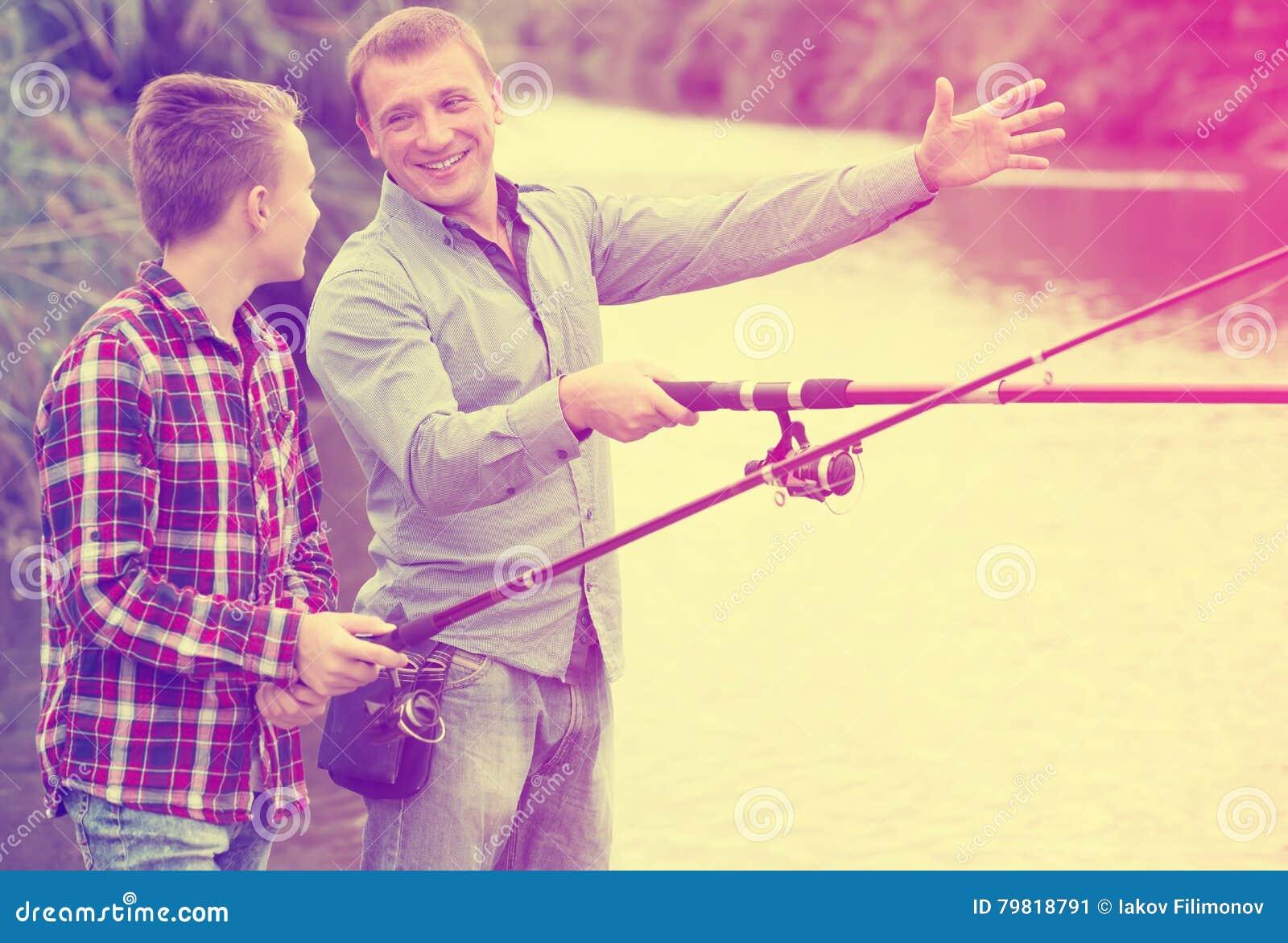 Man och pojke som tillsammans fiskar på den sötvattens- sjön