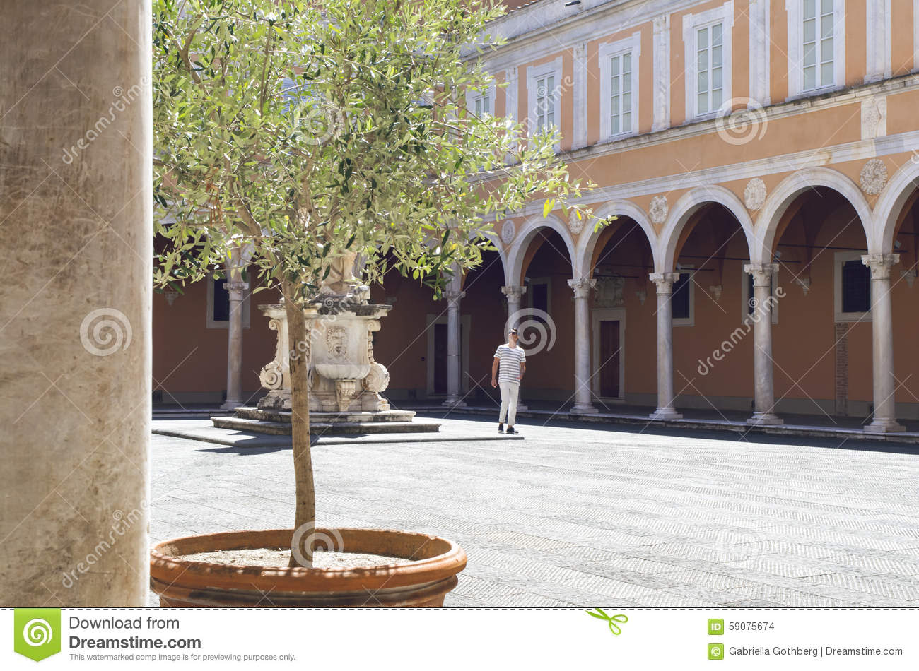 Man in old courtyard with vaults and a statue, in Pisa, Italy.