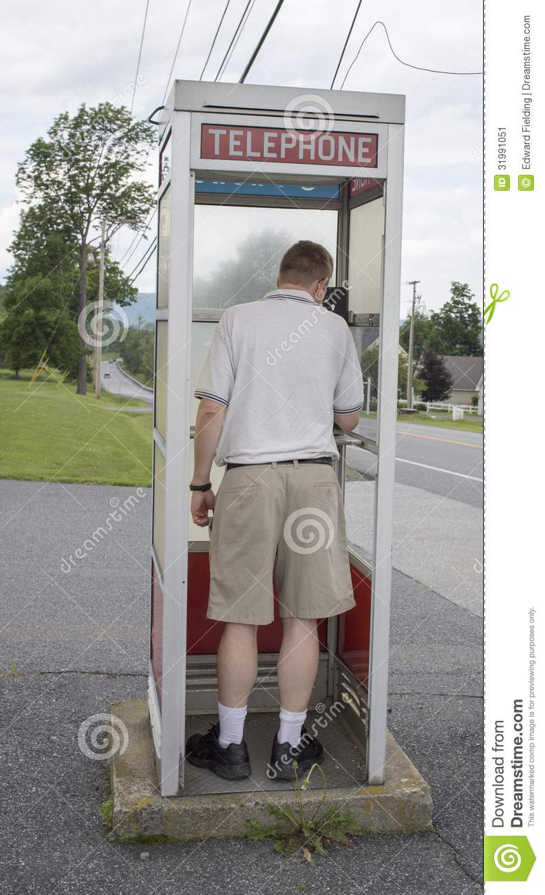 man in a old fashioned vintage pay phone booth editorial