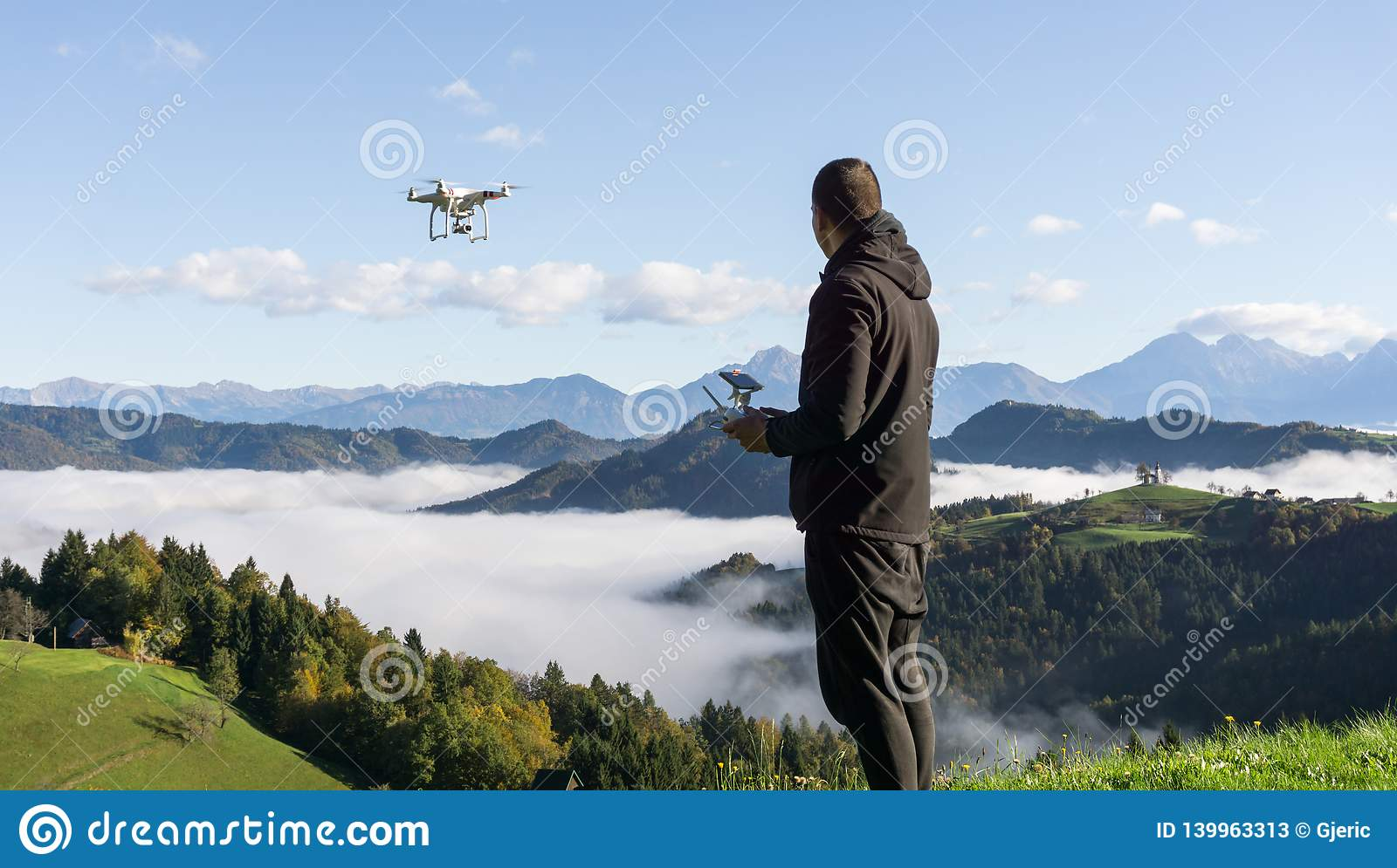 Man operating drone flying or hovering by remote control with beautiful foggy landscape in the background